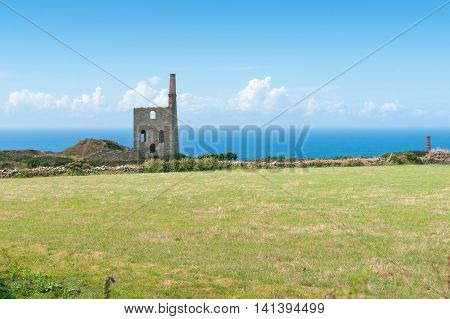 Remains of historic tin mine stone engine house across green field on coast of Cornwall England