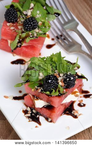 appetizer stacked slices of watermelon feta arugula blackberry sauce and nuts