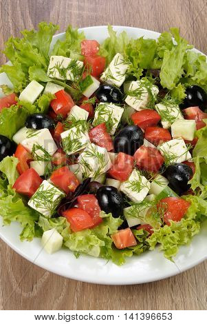Salad of lettuce with diced olives tomato cucumber feta at dill