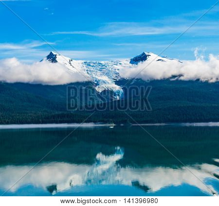 Panorama of one of the many mountain peaks islands and forest areas as seen while cruising the Tracy Arm Fjord in Alaska. Blue sky low clouds calm blue waters reflections of the Tongass National Forest.