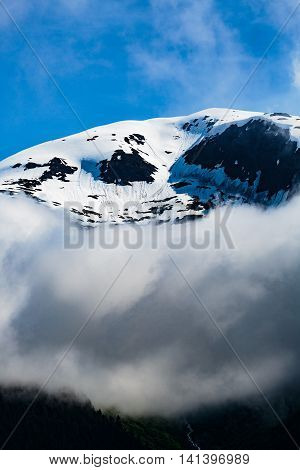 Closeup of one of the many mountain peaks seen while cruising the Tracy Arm Fjord in Alaska. Blue sky low clouds crisp snow and ice reflections of the Tongass National Forest.
