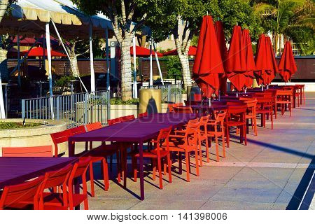 Outdoor furniture including colorful tables and chairs taken at a courtyard in a park