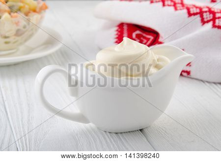 Mayonnaise on a wooden table. Russian style