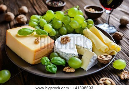 Assorted Cheese Plate With Fruit, Walnuts And Red Vine
