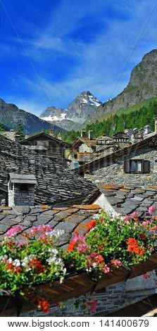 Old alps architecture with flowers in town in Rhemes Notre Dame Valle d'Aosta Italy