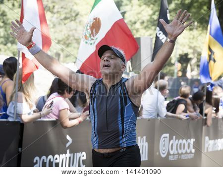 NEW YORK JUL 24 2016: Athlete crossing the finish line of the NYC Triathlon Race in Central Park. The run is 10 kilometers and the race is the only International Distance triathlon in the city.