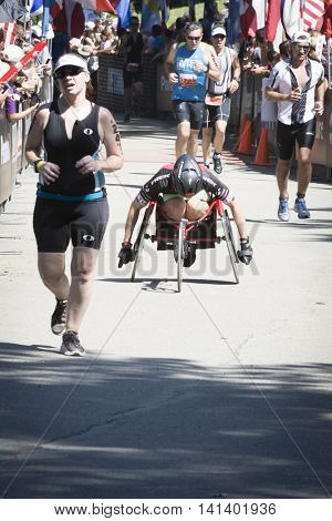 NEW YORK JUL 24 2016: ParaTriathlete in a modified wheelchair approaches the finish line in Central Park in the NYC Triathlon Race, the only International Distance triathlon in the city.