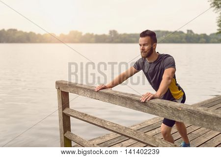 Young Man Doing Stretching Exercises On A Deck