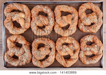 Soft pretzels spread with nuts and sugar holding on brown waxed paper in a stainless steel tray