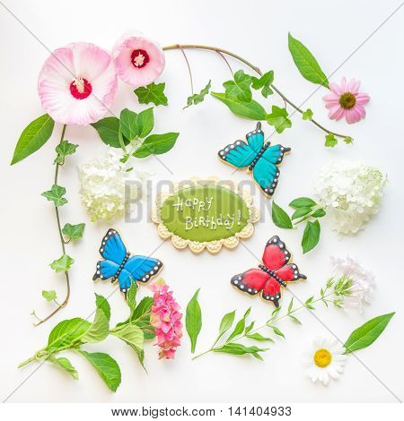 Colorful flowers homemade happy birthday cookie and butterfly shaped cookies composition on light background. Top view flat lay.