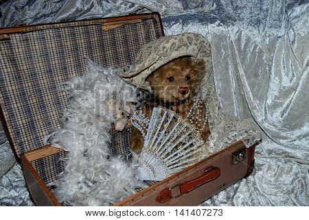 Teddy bear sits in old suitcase with compartments, hat, stole and jewelry