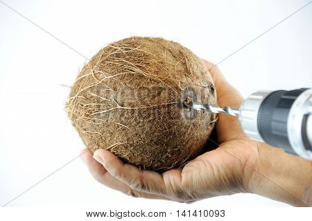 Using electrical drill to drill on coconut