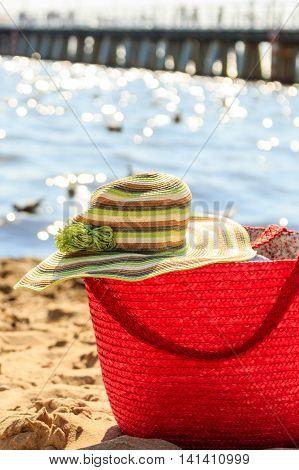 Wicker basket handbag bag purse and hat on beach sand. Summer holiday vacation.