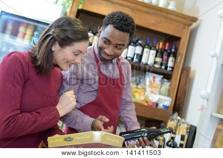salesman in winery advising her smiling customer