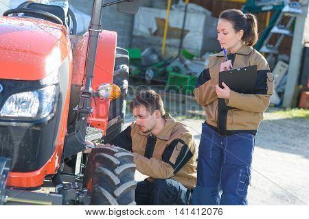 mechanicians examining tractors engine