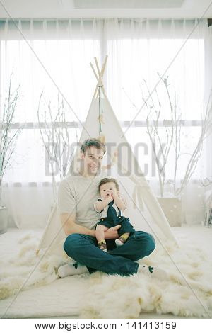 Happy Father holding Adorable baby  boy son while sitting in a wigwam