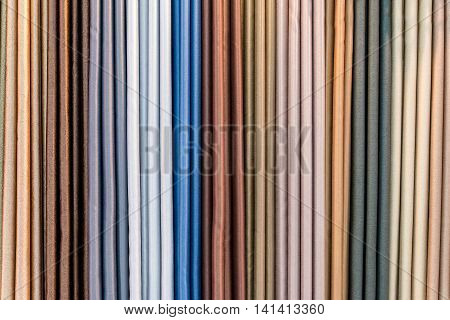 Colorful curtain samples hanging from hangers on a rail in a display in a retail store.Curtain background.