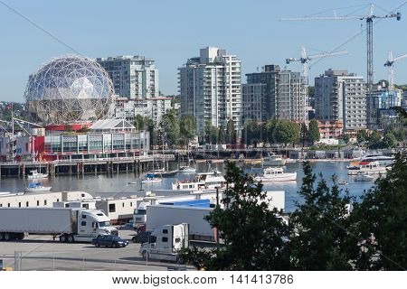 Vancouver Canada - July 24 2016: The TELUS Science Museum and Kaleidoscope sitting at the end of the recreational harbor off English Bay. Pleasure vessels on the water. Trucks in front. Apartment buildings as background.