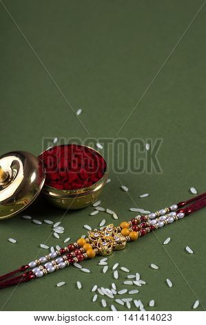 A Rakhi with rice grains and kumkum. Raksha Bandhan Festival. Indian festival background.