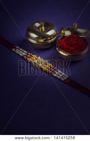 A Rakhi with rice grains and kumkum. An Indian festive background.