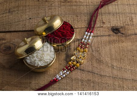 A Rakhi with rice grains and kumkum. An Indian festive background. Raksha Bandhan or Rakhi.