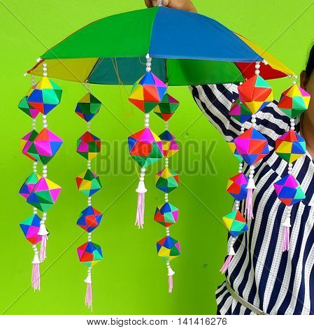 teacher holding up homemade multicolored umbrella mobile with hanging strings of construction paper cubes made with colored triangles, school project in Songhkla, Thailand