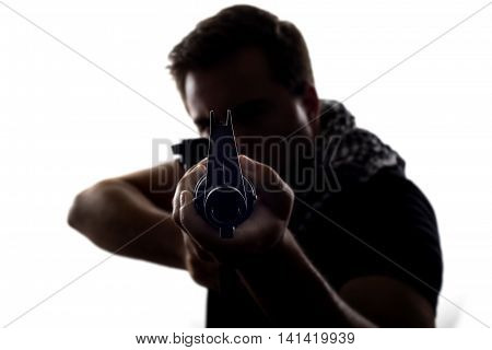 Silhouette of a model posing as a military soldier with a rifle and shemagh scarf