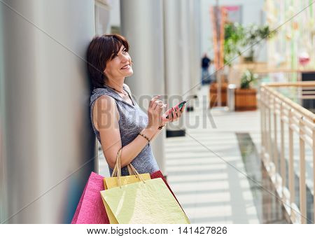 Shopping woman with bags with phone at the mall