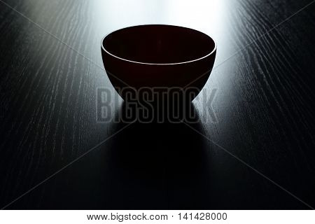let everyone fill his cup of happiness and good  round dish standing on a black table. bright back-light