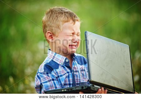 Little boy crying bitterly, holding the laptop