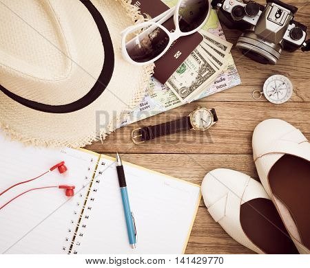 Travel concept with digital camera straw hat sunglasses world map compass passport money wristwatch earphones shoes notepad and pen on wooden table