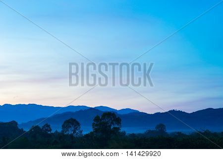Misty Morning Sunrise Of Hilly Area With Ray Of Light.