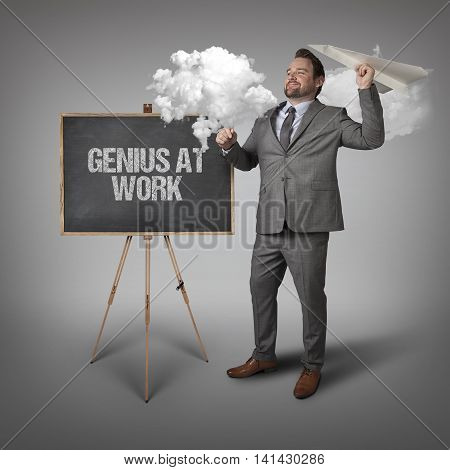 Genius at work text on blackboard with businessman and paper plane