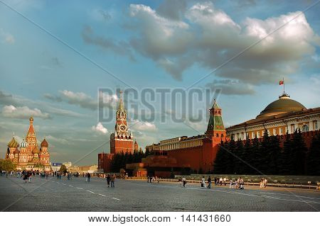 Red Square of Moscow in the summer day. Red wall of the Kremlin Spassky Savior's tower St. Basil's cathedral and Lenin's mausoleum.