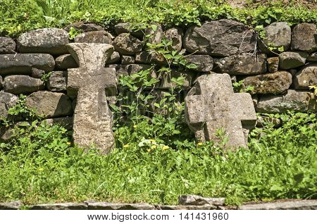 Old stone tombstone crosses on stone wall background