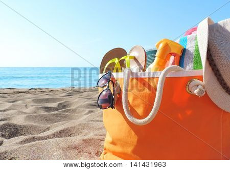 Beach bag with sunglasses, summer hat, shoes and suntan lotion. Beach life.