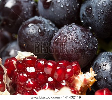 juicy fresh black grapes with red garnet