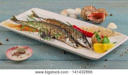 Healthy grilled ready-to-eat seafood on the white plate on the blue wooden table