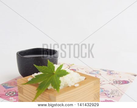 Beautiful sake (rice wine) cup of earthenware, Blur rice and maple, Japanese paper, on bright white background