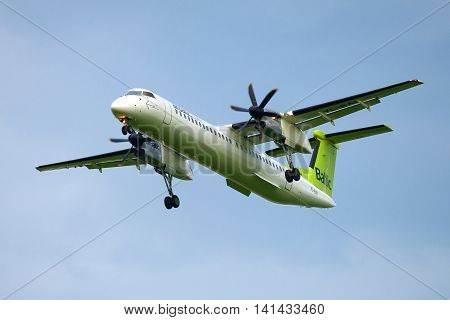 SAINT PETERSBURG, RUSSIA - JULY 03, 2016: The Bombardier Dash 8-Q402 (YL-BAI) airlines Air Baltic in a cloudy sky