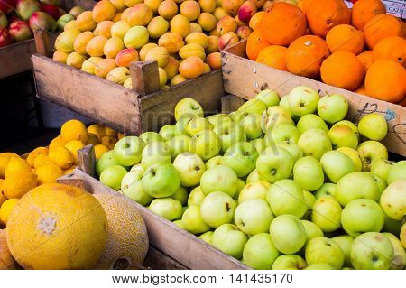 Apples tangerines melon apricots on a market stall