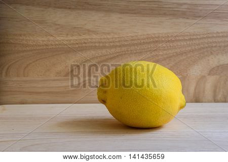 One yellow lemon on wooden background. Contains vitamins. Useful for colds.