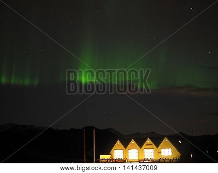 Started having northern lights or aurora borealis above yellow cottage at jokulsarlon glacier lagoon in Iceland