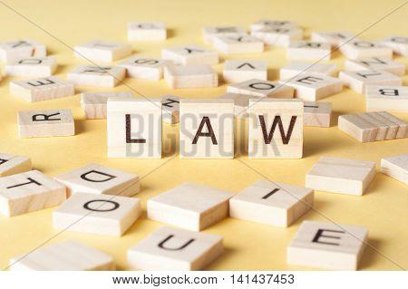 Law word written on wood block. Woodwn abc.