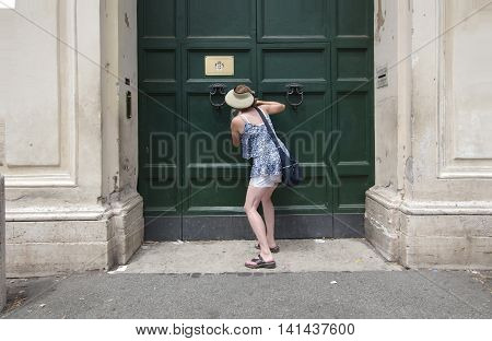 ROME ITALY - JULY 23 2016: Tourist peeps into the keyhole of the Villa Magistrale dei Cavalieri di Malta Rome Italy
