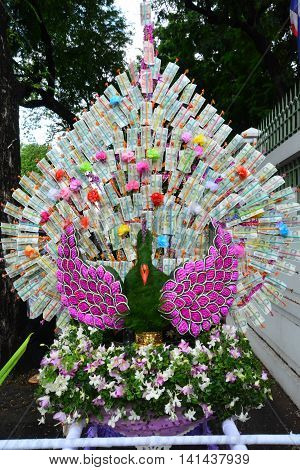 Money decorate is peacock at a buddhist temple in Thailand where financial donations are placed in order to receive merit and good fortune
