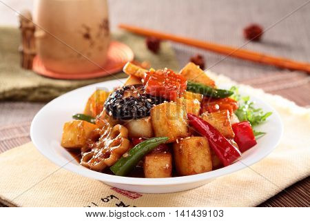 Lotus root simmered tofu with mushroom chili and sliced lotus on white plate