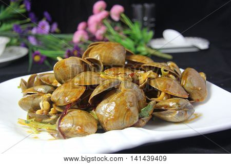 Spicy clams with vegetable on white plate in black background
