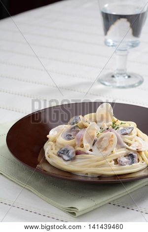 Bonggolre cream sauce pasta with clams on black plate with glass of water