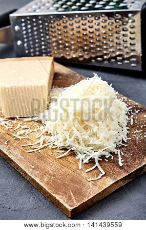 Piece and grated parmigiano reggiano or parmesan cheese on wood board on checkered napkin . Grated parmesan uses in pasta dishes, soups, risottos and grated over salads.